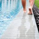 Close up man walking barefoot next to hotel swimming pool