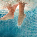 detail of kid feet on a  swimming pool